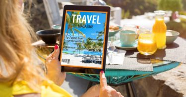 Woman reading travel magazine on tablet computer.